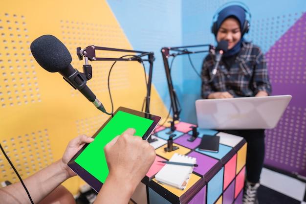 Muslimische asiatische frau und mann sprechen zusammen im podcast-studio