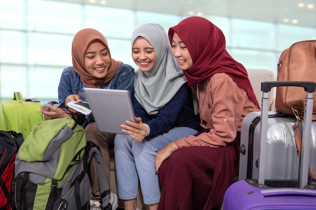 Muslimische asiatische freundin, die im flughafenterminal sitzt