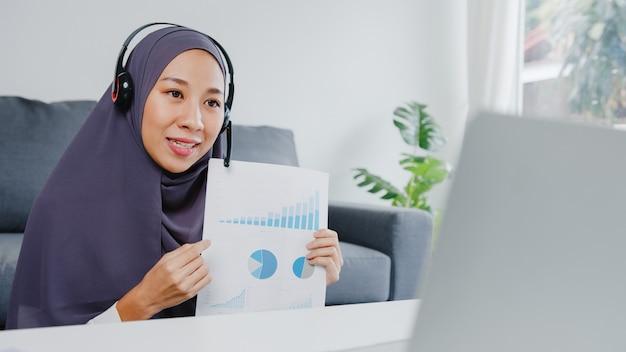 Muslimische dame tragen kopfhörer mit laptop sprechen mit kollegen über verkaufsbericht in konferenz-videoanrufen, während sie von zu hause im wohnzimmer arbeiten.
