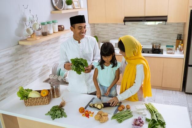 Muslimische eltern und kinder kochen und bereiten sich gemeinsam auf das iftar-abendessen in der küche vor