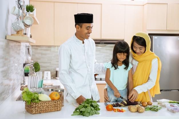 Muslimische eltern und kinder kochen und bereiten sich gemeinsam auf das iftar-abendessen in der küche während des ramadan-fastens vor