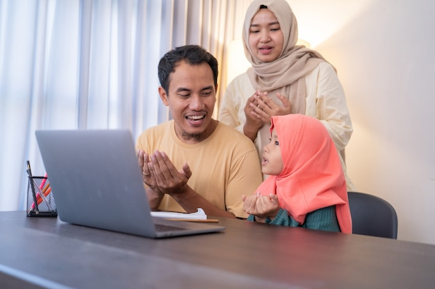Muslimische eltern und tochter beten zusammen, während sie zu hause einen laptop benutzen
