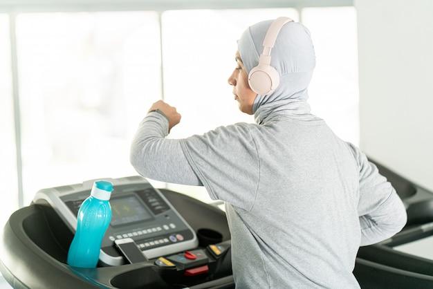 Muslimische erwachsene frau mit kopfhörern auf laufband