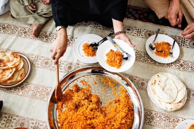 Muslimische familie beim abendessen auf dem boden