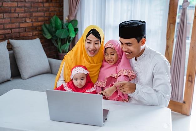 Muslimische familie mit laptop, um freunde anzurufen