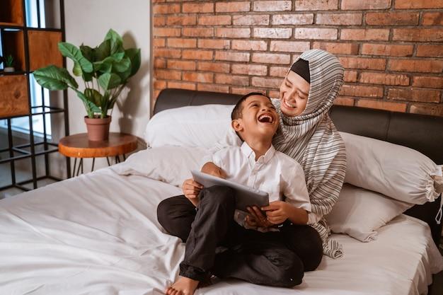 Muslimische familie mit tablette auf dem bett