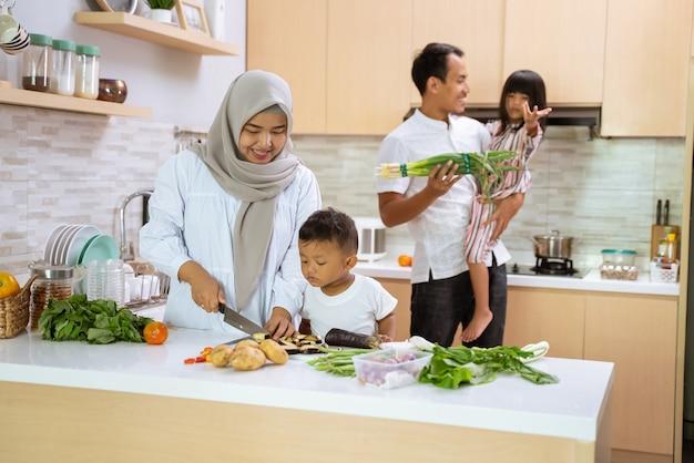 Muslimische familie mit zwei kindern, die zu hause zusammen kochen, sich auf das abendessen und das fastenbrechen vorbereiten