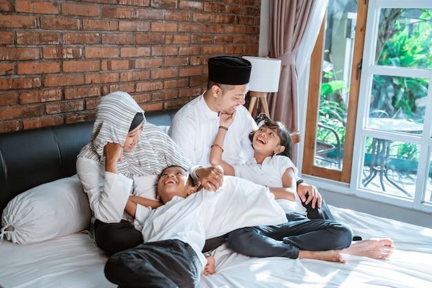 Muslimische familien mit ihren kindern entspannen sich und scherzen auf dem bett