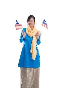 Muslimische frau aufgeregt, die flagge von malaysia lokalisiert über weißem hintergrund hält