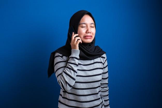 Muslimische frau bekommt schlechte nachrichten, wenn sie am telefon spricht, trauriger weinender ausdruck vor blauem hintergrund