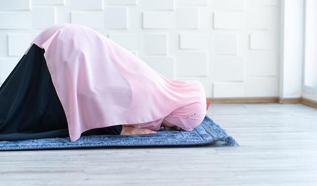 Muslimische frau beten auf hijab, der auf matte drinnen betet