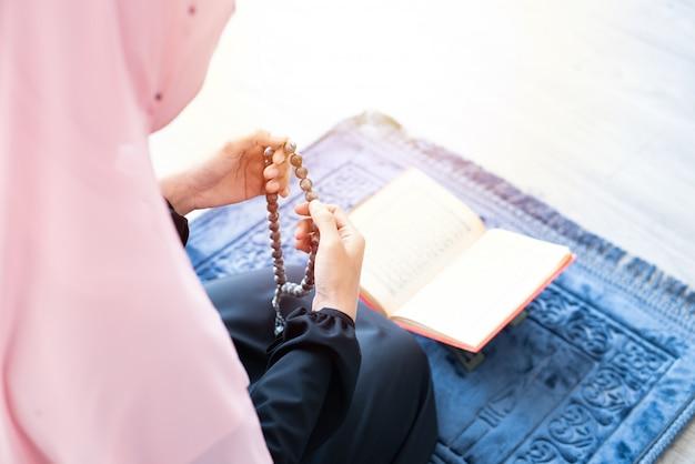 Muslimische frau beten mit perlen und lesen koran