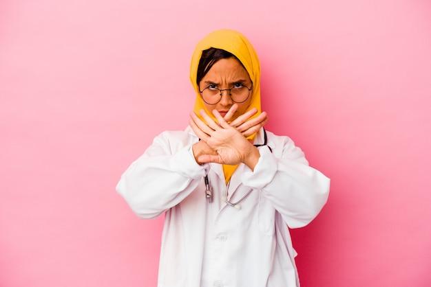 Muslimische frau des jungen doktors lokalisiert auf rosa wand, die eine verweigerungsgeste tut