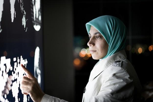 Muslimische frau, die am intelligenten infografikbildschirm arbeitet