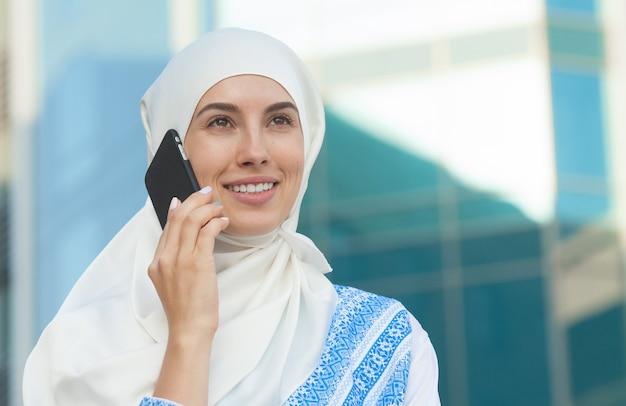 Muslimische frau, die am telefon spricht