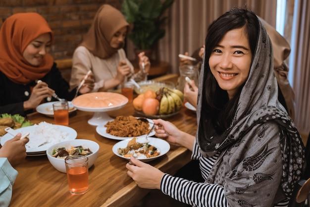 Muslimische frau, die beim abendessen lächelt
