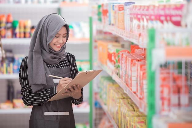Muslimische frau, die das produkt im laden prüft