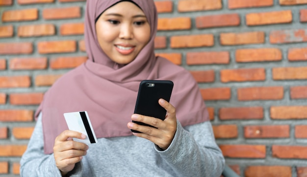 Muslimische frau, die ein handy und eine kreditkarte für den einkauf in der entspannenden zeit hält