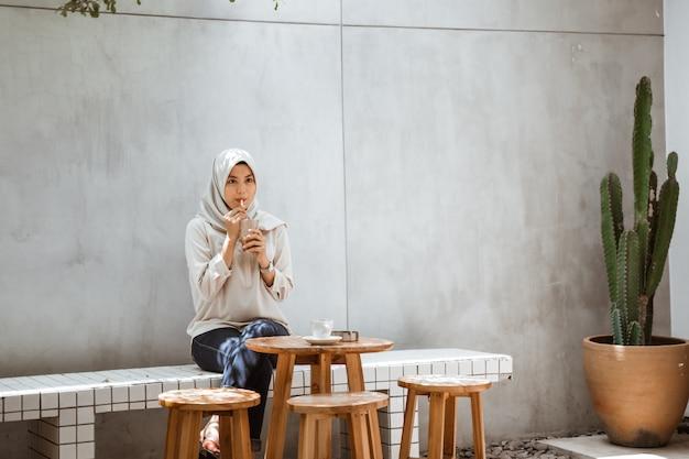 Muslimische frau, die eiskaffee genießt