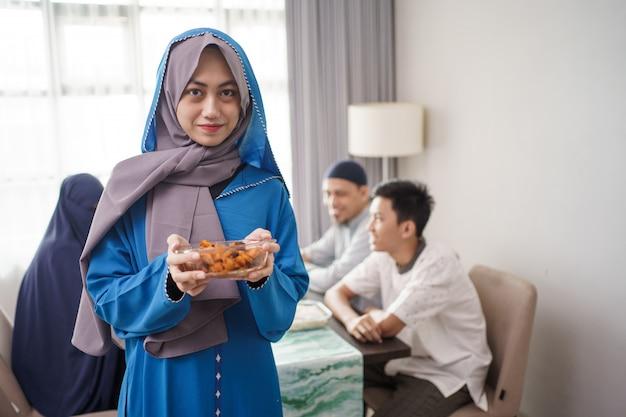 Muslimische frau, die essen für familie dient