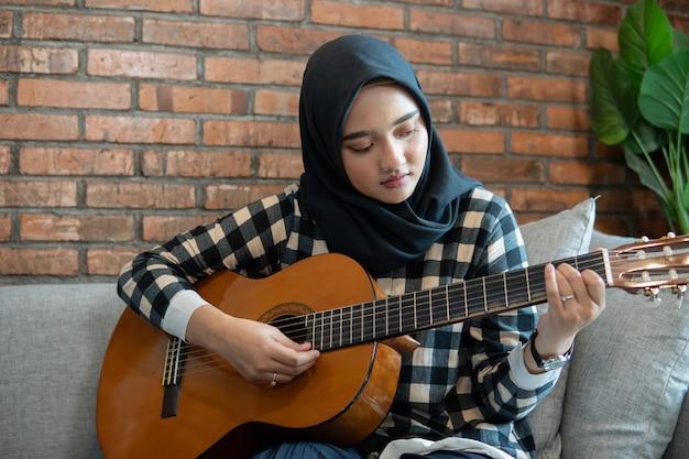 Muslimische frau, die gitarre spielt