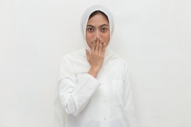 Muslimische frau, die hijab trägt, schockierte, mund mit händen für fehler zu bedecken geheimes konzept