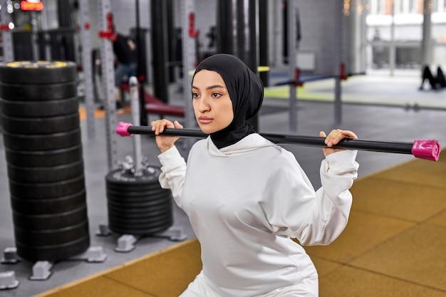 Muslimische frau, die hijab trägt und kniebeugen mit krafttraining macht, um in zukunft fit, sportlich und gesund zu sein. junge frau konzentriert sich auf fitness