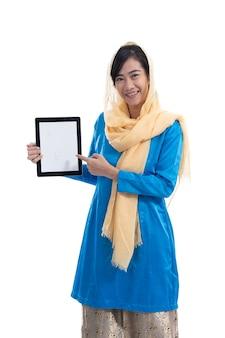 Muslimische frau, die ihren tablett-pc-bildschirm lokalisiert über weiß zeigt