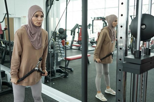 Muslimische frau, die im fitnessstudio trainiert