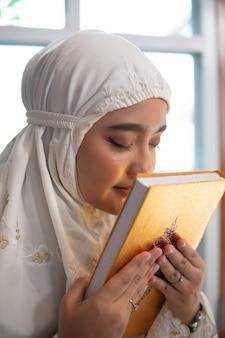 Muslimische frau, die koran küsst