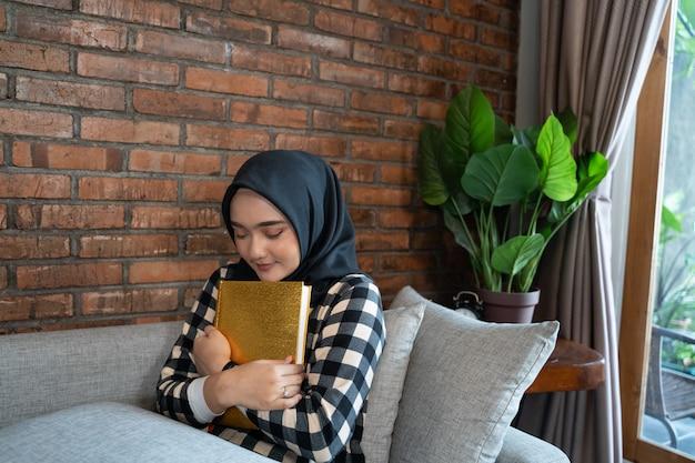 Muslimische frau, die koran umarmt