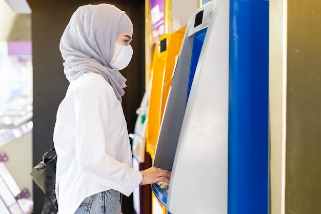 Muslimische frau, die medizinische maske trägt, um infektionsviren zu verhindern, die geldautomaten verwenden, um geld auf stadtstraße abzuheben.