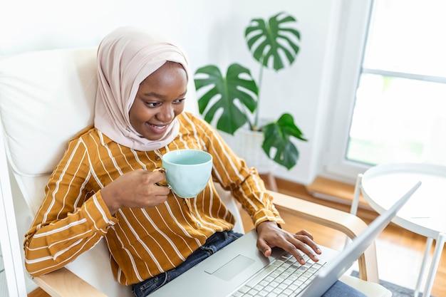 Muslimische frau, die mit computer arbeitet. arabisch junge geschäftsfrau, die zu hause an ihrem schreibtisch sitzt, an einem laptop-computer arbeitet und kaffee oder tee trinkt. muslimische frau, die zu hause arbeitet und computer benutzt.