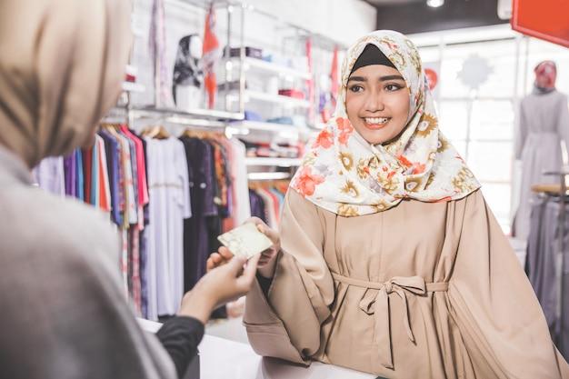 Muslimische frau, die mit kreditkarte zahlt
