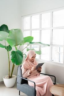 Muslimische frau, die mit tablette beim entspannen durchsucht