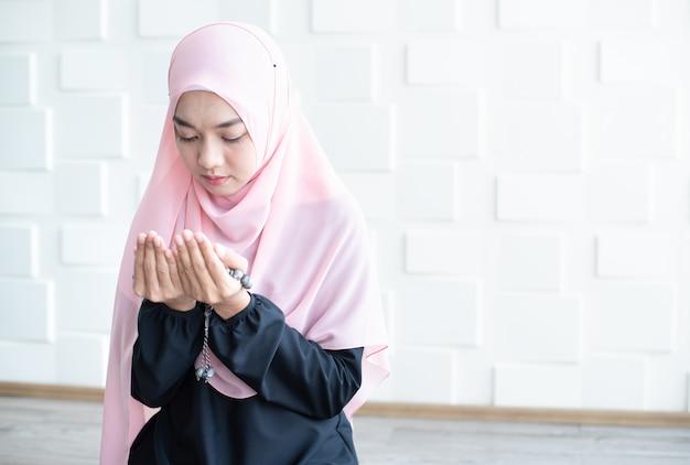 Muslimische frau, die nahe lichtwand betet