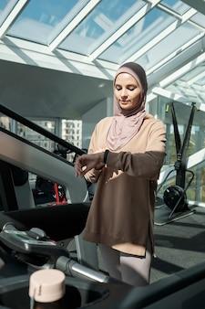 Muslimische frau, die sich den aktivitätstracker anschaut