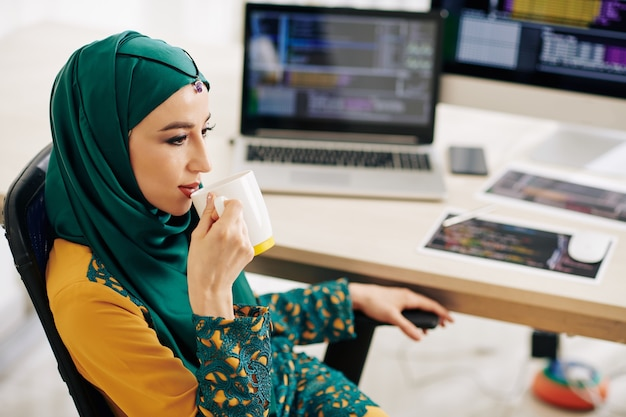 Muslimische frau, die tee trinkt