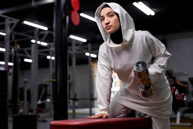 Muslimische frau, die übungen mit hanteln macht, selbstbewusste frau, die sich auf das training konzentriert, steht zur seite und hält schweres gewicht in händen