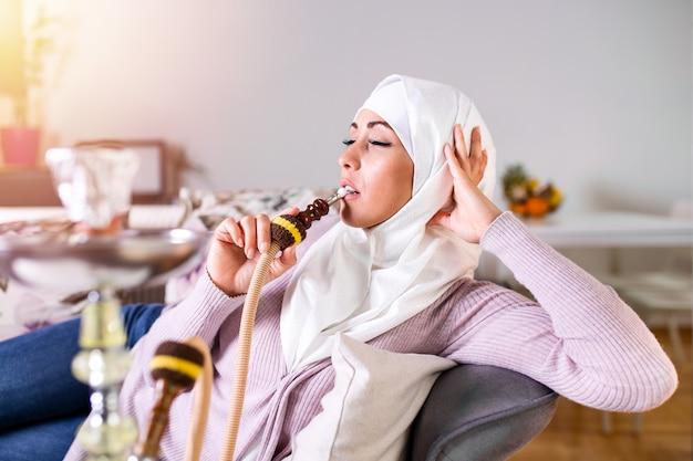 Muslimische frau, die zu hause shisha raucht und beim rauchen von nargile genießt.