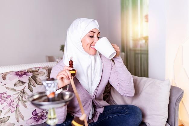 Muslimische frau, die zu hause shisha raucht und kaffee oder tee trinkt. arabisches mädchen raucht shisha