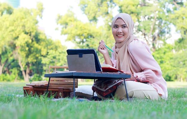 Muslimische frau entspannen und arbeiten im park im urlaub