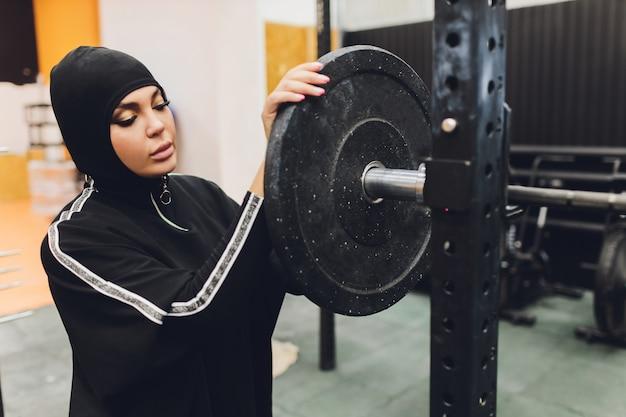 Muslimische frau im hijab, der in einem fitnessstudio trainiert.