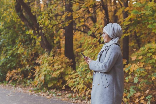 Muslimische frau im park mit smartphone-verbundenem online-werberaum für werbung