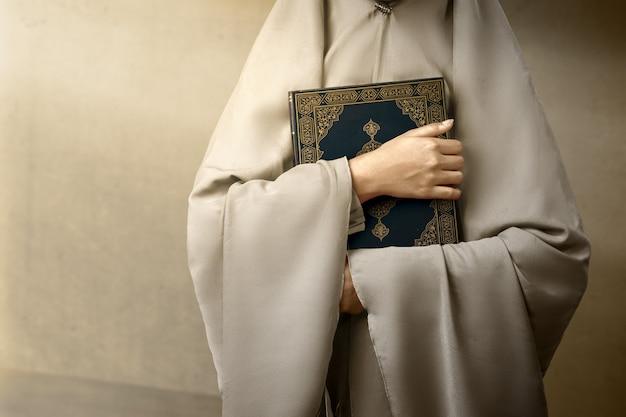 Muslimische frau in einem schleier, der den koran mit grauem wandhintergrund steht und hält