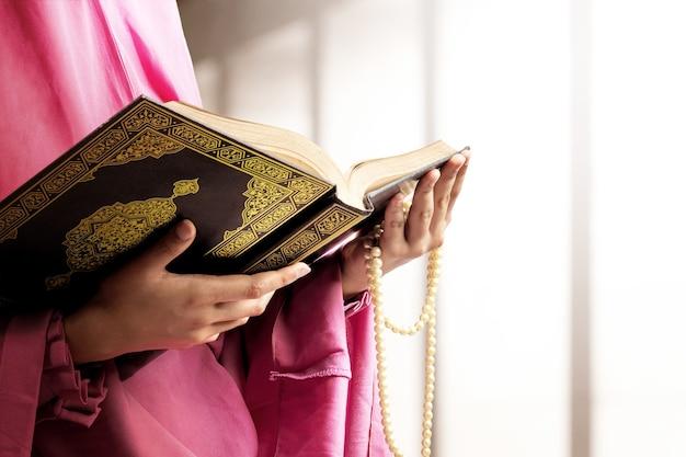 Muslimische frau in einem schleier, der gebetsperlen und den koran auf der moschee hält