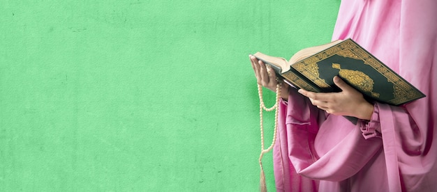 Muslimische frau in einem schleier, der gebetsperlen und den koran mit grünem wandhintergrund hält