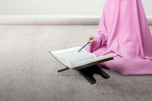 Muslimische frau in einem schleier, der sitzt und den koran liest