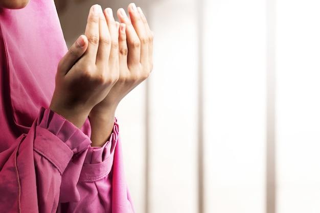 Muslimische frau in einem schleier stehend, während erhobene hände und auf der moschee betend