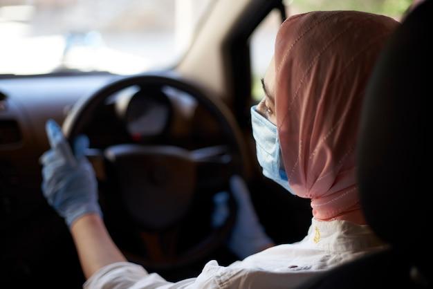 Muslimische frau in gesichtsmaske und handschuhen, die auto fahren